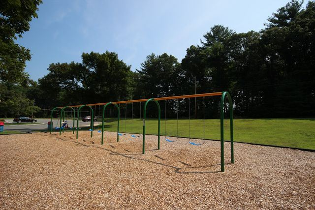 Swingset in playground with parking lot in background