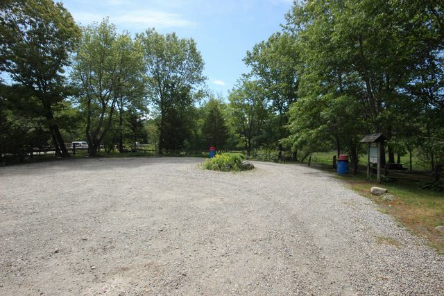 Gravel parking lot driveway with tree surrounding it and Landing display board in background